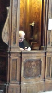 Sacerdote en un confesionario de Santa María La Mayor jugando con el móvil.