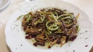 Ensalada de puntarelle, alcachofas y carne braseada.